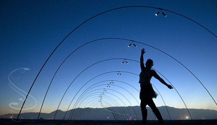 Monique dancing inside a wonderful tube of light and shape at sunset on the playa. My wife threw away our booklet accidentially when we got back, so I don
