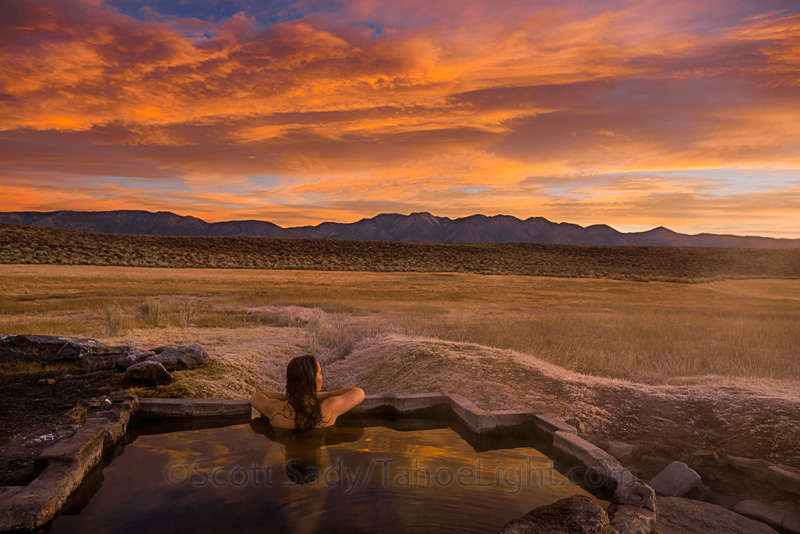 woman in hotspring in desert at sunrise